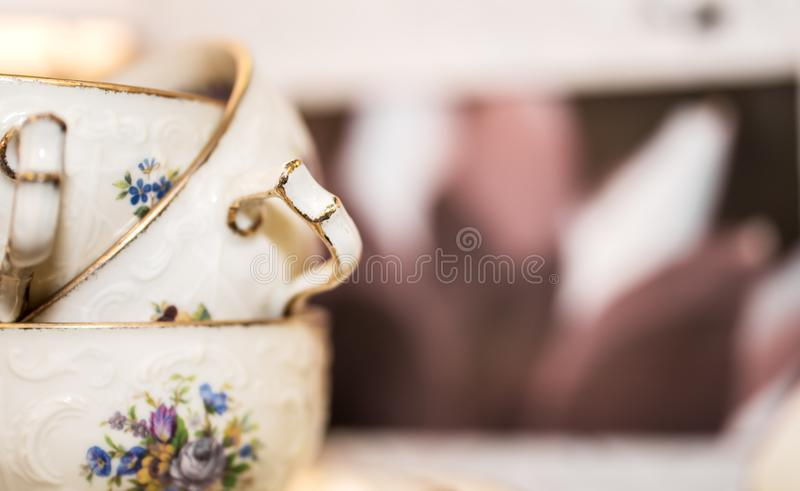 Stack of porcelain coffee cups with gold rim and floral design on white pink background. Vintage. Concept royalty free stock images