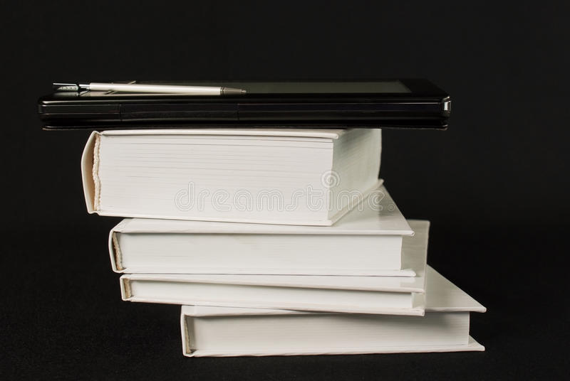 Stack of printed books with electronic book reader stock photo