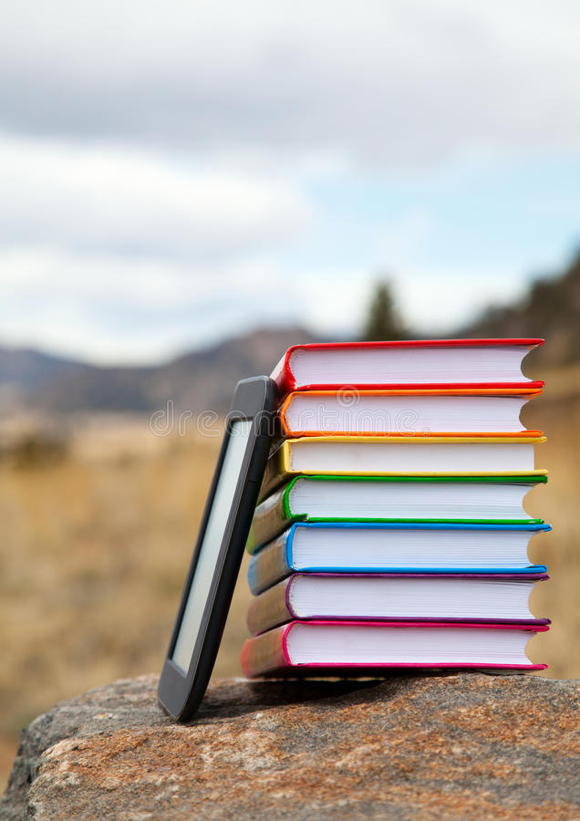 Stack of printed books with electronic book reader royalty free stock images