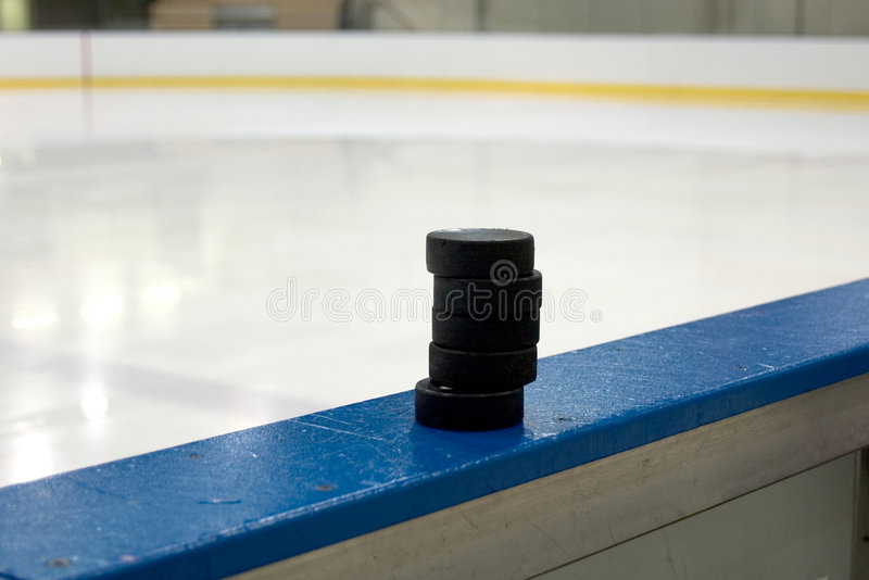 Stack of pucks. A stack of hockey pucks sits on the wall of the team bench of a rink. Photographed looging toward the ice just after the zamboni finished cutting