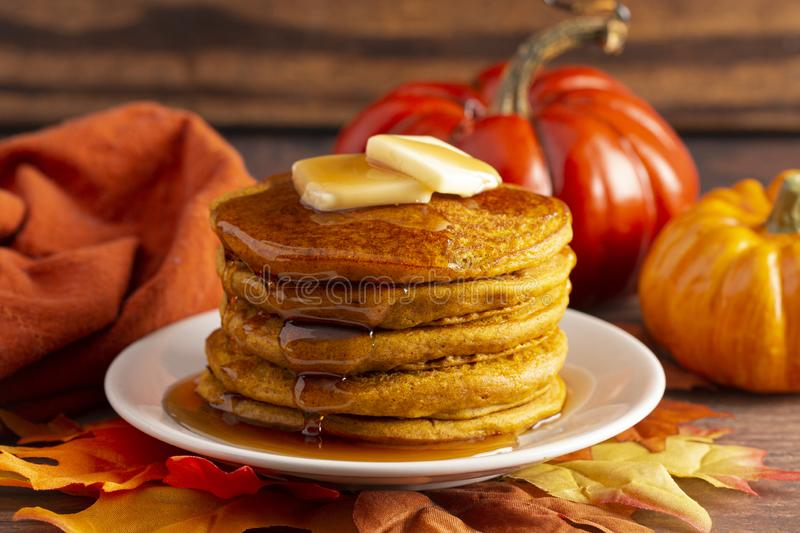 Stack of Pumpkin Spice Flavored Pancakes on a Wooden Table. A Stack of Pumpkin Spice Flavored Pancakes on a Wooden Table royalty free stock images