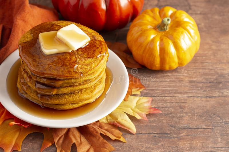 Stack of Pumpkin Spice Flavored Pancakes on a Wooden Table. A Stack of Pumpkin Spice Flavored Pancakes on a Wooden Table royalty free stock photo