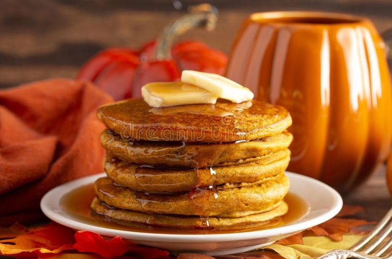 Stack of Pumpkin Spice Flavored Pancakes on a Wooden Table. A Stack of Pumpkin Spice Flavored Pancakes on a Wooden Table stock photo