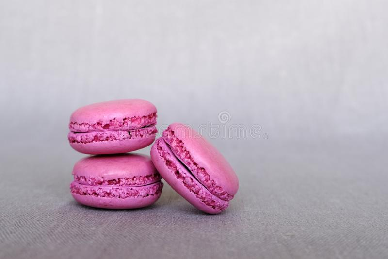 Stack of purple blackberry macarons on grey background, copy space stock photo