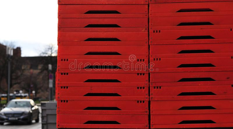 Stack of red foldable plastic boxes. Red foldable plastic boxes stacked up on sidewalk in a city street stock photography