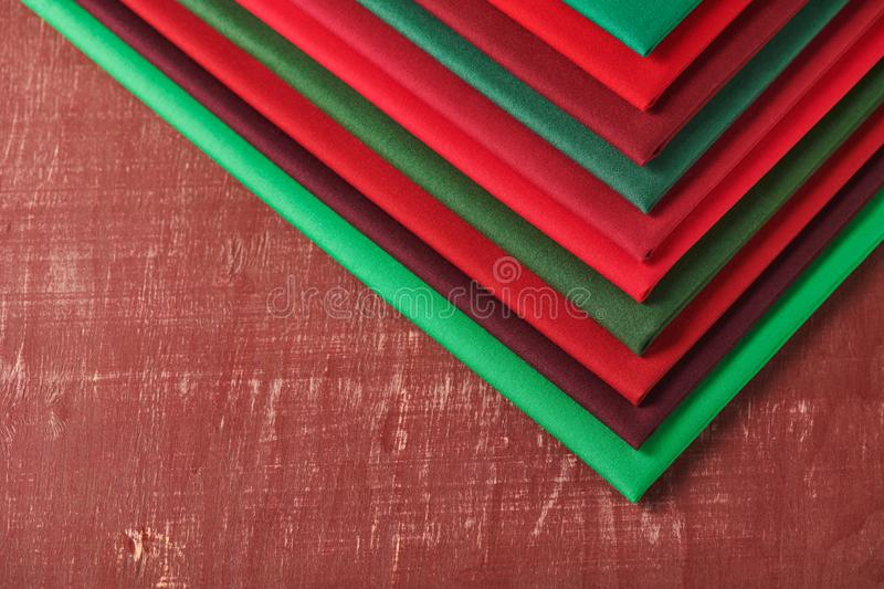 Stack of red and green fabrics on brown background, space for text royalty free stock image