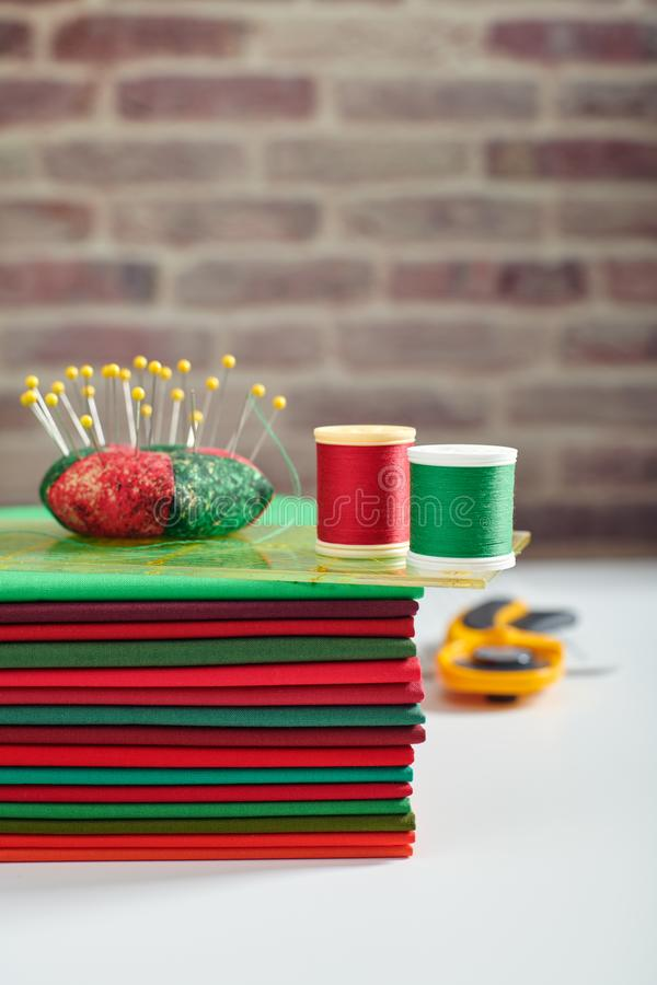 Stack of red and green fabrics, sewing and quilting accessories on brick wall background stock photography