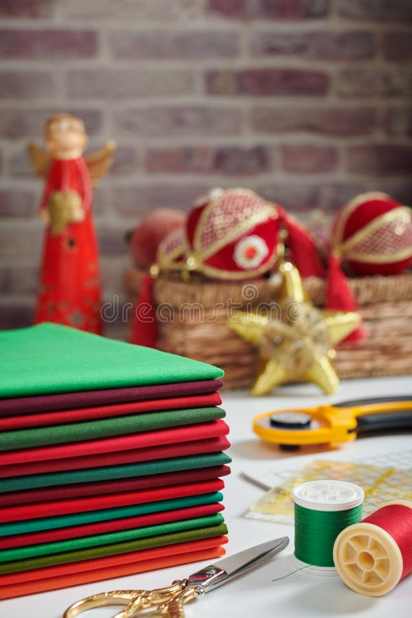 Stack of red and green fabrics, sewing and quilting accessories on Christmas decorations background stock photography