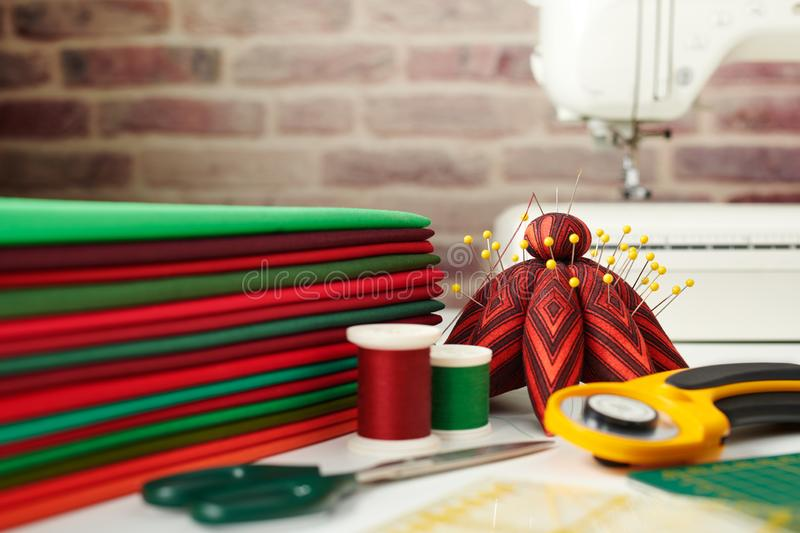 Stack of red and green fabrics, sewing and quilting accessories and sewing machine on brick wall background royalty free stock photography