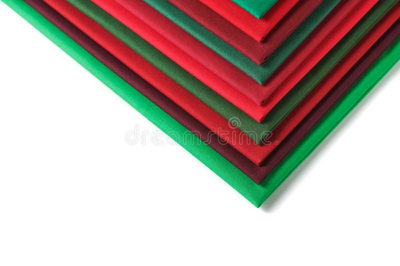 Stack of red and green fabrics on white background, space for text stock image
