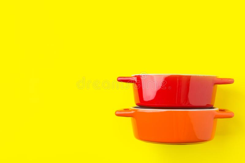 Stack of red and orange ceramic cocottes on bright yellow background. Cooking baking cookware concept. Workshop poster banner royalty free stock photography