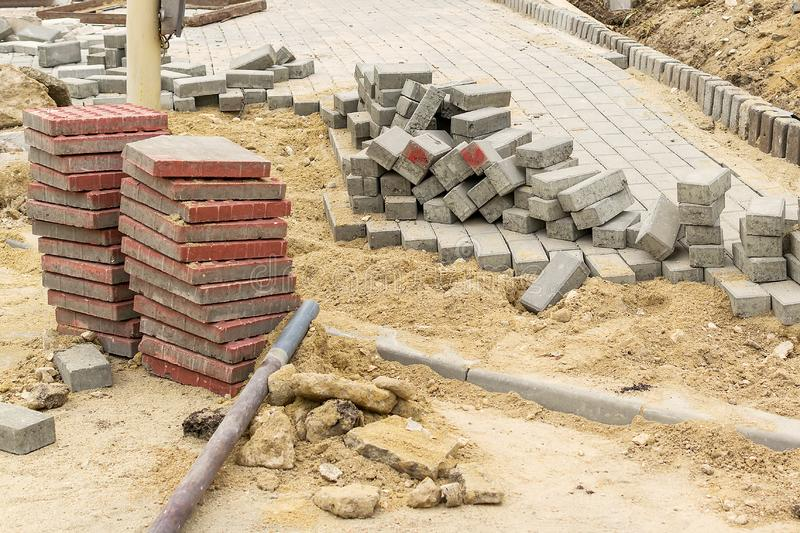 Stack of red pavement stones at the site of the road works. Construction and repair of the sidewalk. Improvement of city streets royalty free stock photos