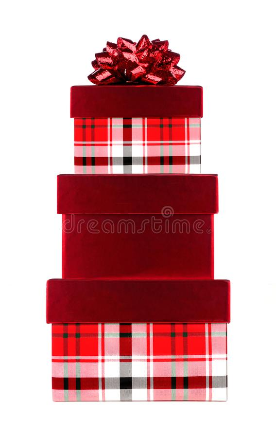 Stack of red and plaid Christmas gift boxes with red bow isolated on white stock photos