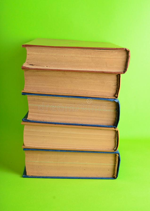 Stack of retro books on a green background. Horizontal photo. Stack of old books on a green background. Horizontal photo stock image