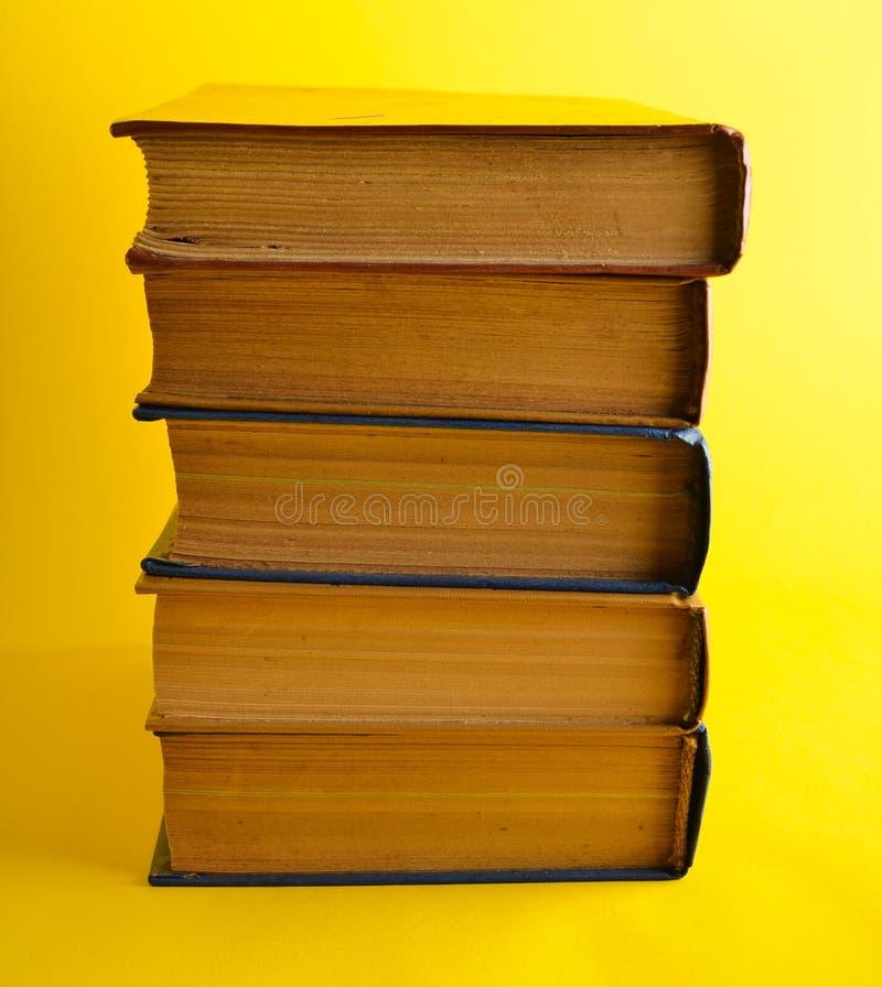 Stack of retro books on yellow background. Horizontal photo.  stock photos