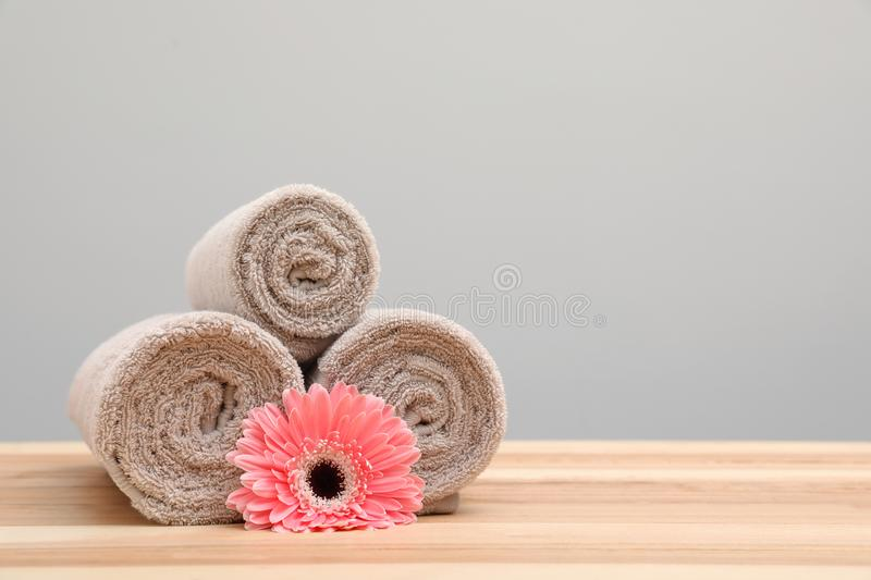 Stack of rolled towels and flower on table. royalty free stock image
