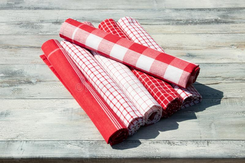 Stack of rolled up red white checkered and striped linen tableclothes on rustic bright wooden table.Outdoor. royalty free stock photography