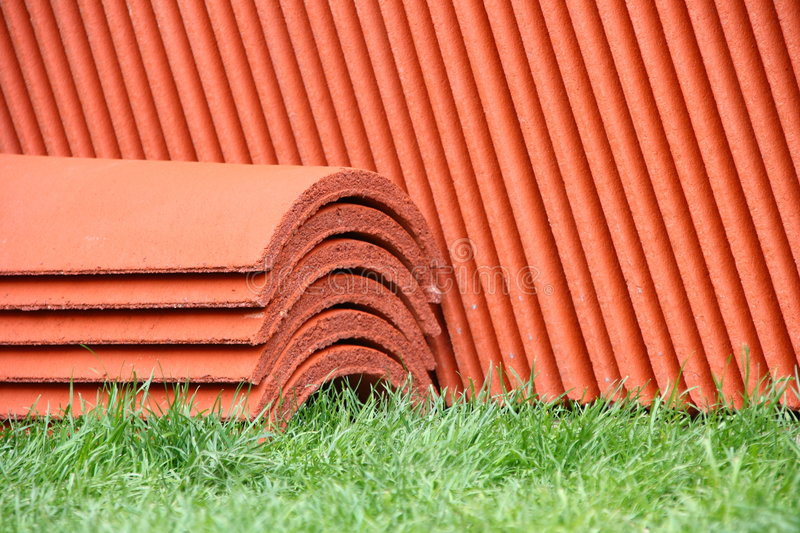 Stack of roof-tiles. On green grass stock photography