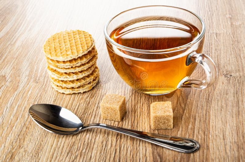 Stack of round wafers with filling, spoon, sugar, cup of tea on wooden table royalty free stock images