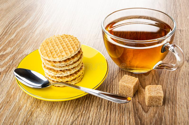 Stack of round wafers with filling, spoon in saucer, sugar, cup of tea on wooden table royalty free stock photo