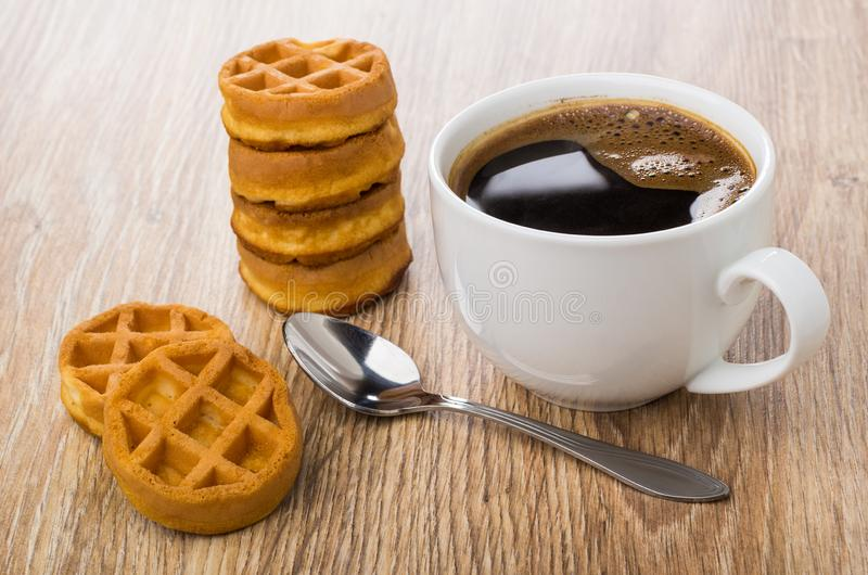 Stack of round waffles, cup of coffee, spoon on table royalty free stock photography