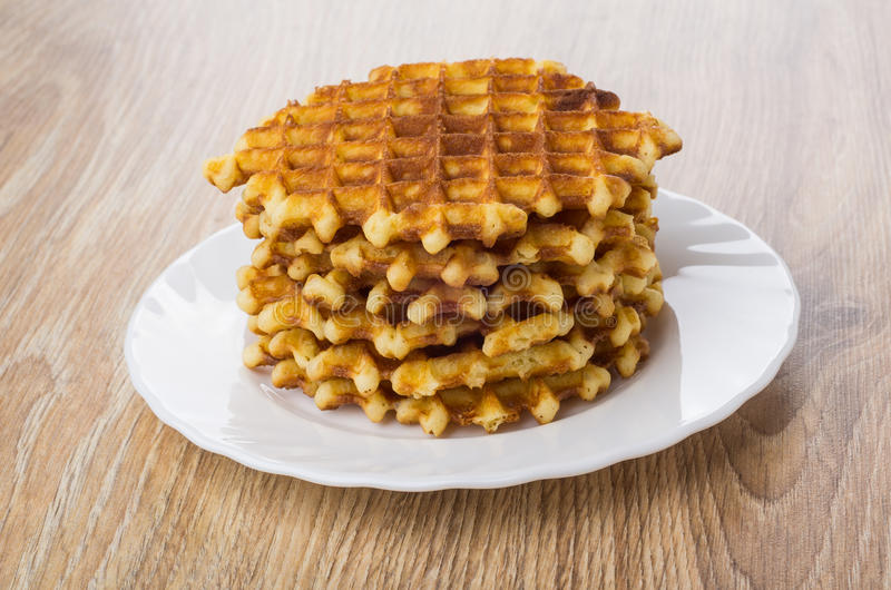 Stack of round waffles in white plate on table stock image