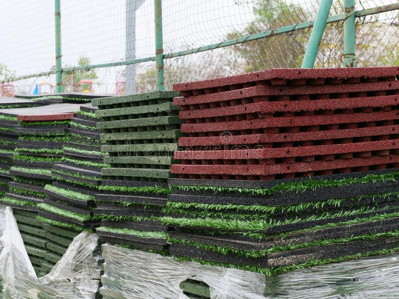Stack of rubber floor tile mats and artificial turf grass rug tiles for elastic safety flooring. Eco safety surfacing mats are a. Low cost solution and reduce stock photography