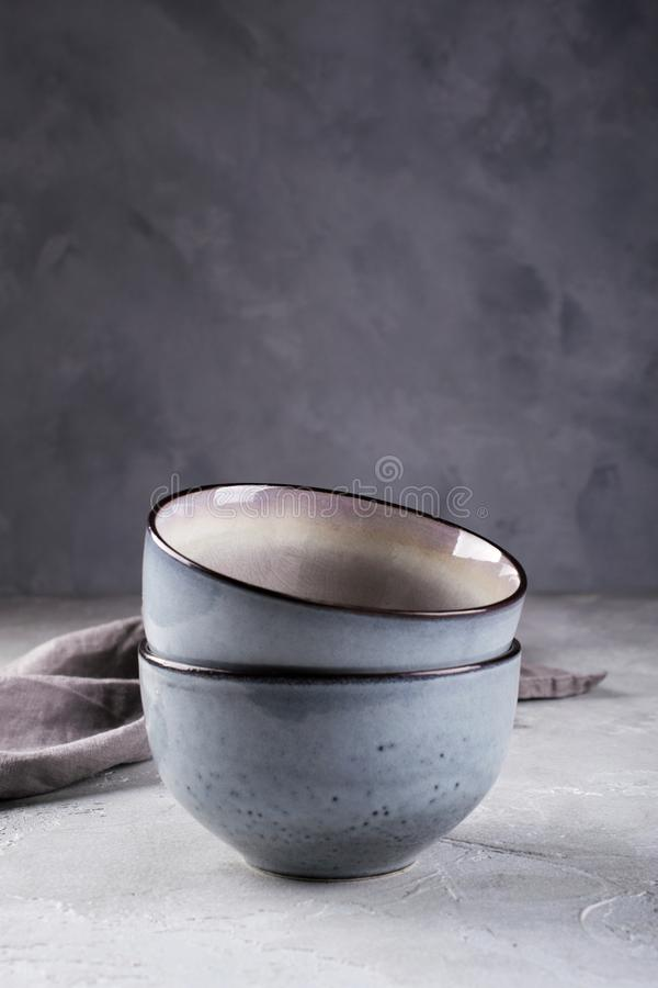Stack of rustic style handcraft bowls in neutral tones against shabby grey wall. stock photography