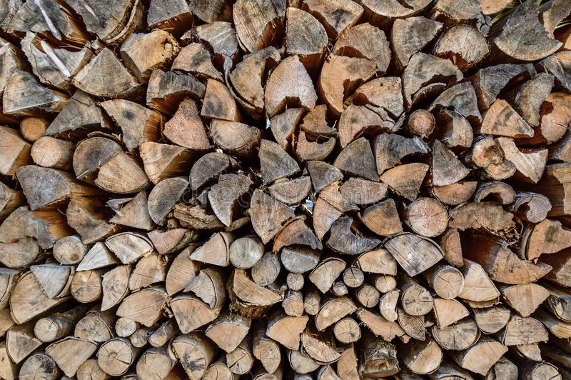 Stack of sawn tree logs. Stacked pile of firewood logs. Lumber industry. Wooden background. Stack of sawn tree logs detail. Stacked pile of wood logs stored for stock photography