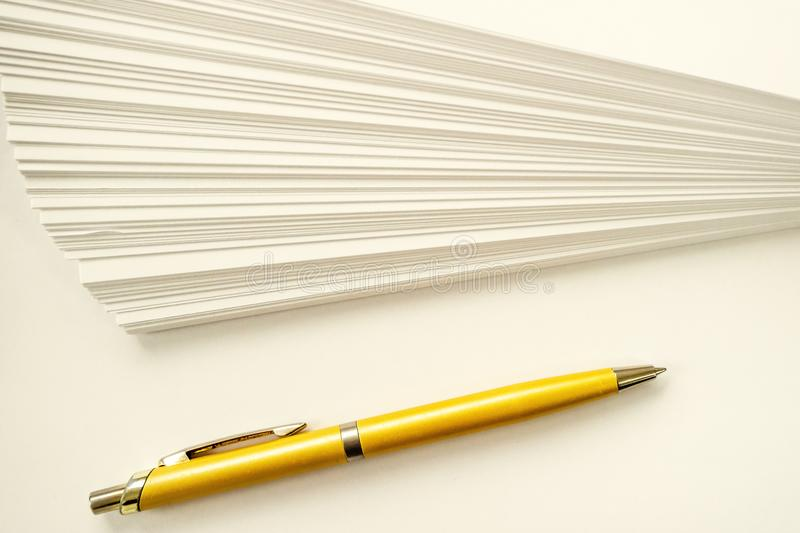 A stack of sheets of white paper and ball point gold pen. Writing set royalty free stock photos