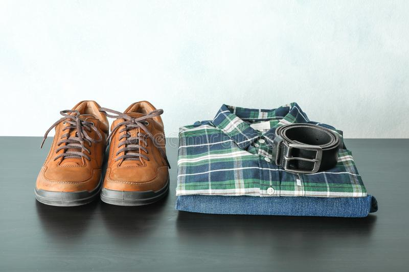 Stack of shirt, jeans and belt with shoes on table against light background. Space for text stock photos