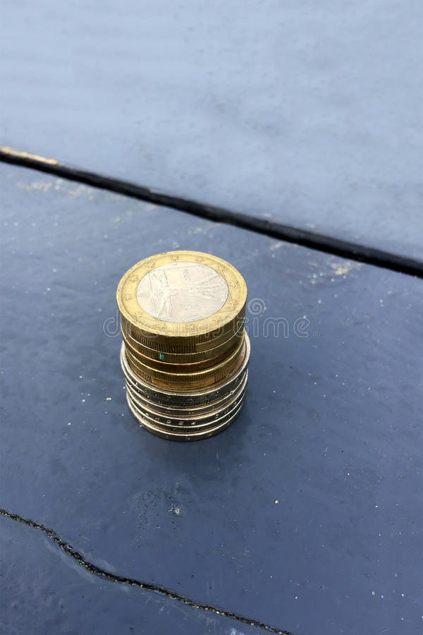 Stack of small change Euro money coins. On blue table stock photography