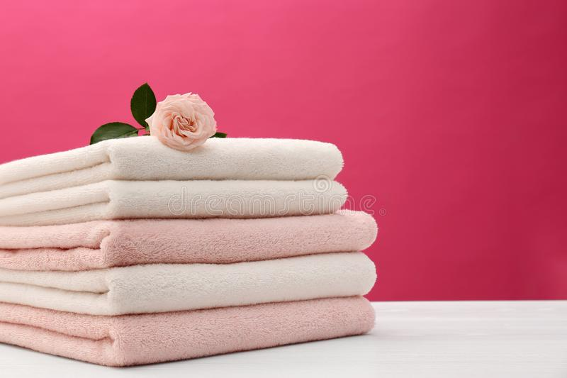 Stack of soft clean towels with beautiful flower on table against color background. Space for text stock photography