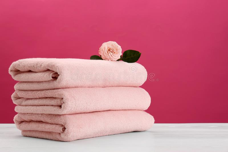 Stack of soft clean towels with beautiful flower on table. Against color background. Space for text royalty free stock images
