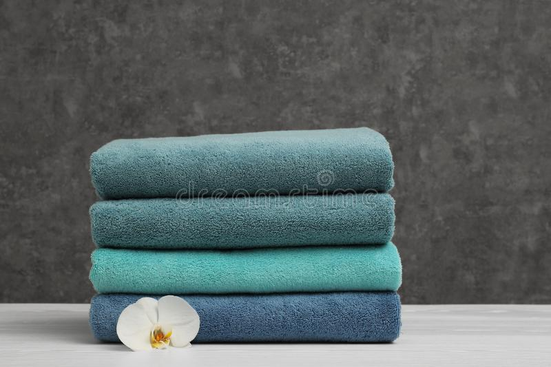 Stack of soft clean towels with beautiful flower on table. Space for text royalty free stock photography