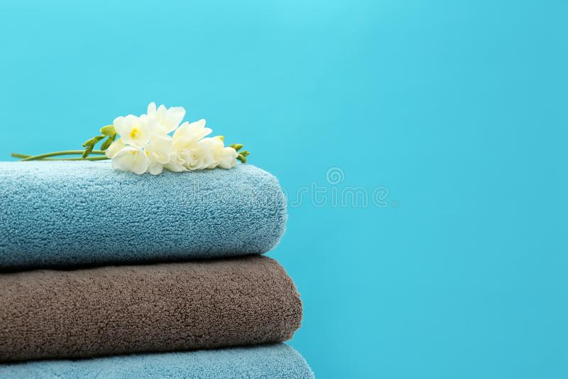 Stack of soft clean towels with beautiful flowers on color background. Space for text royalty free stock photography