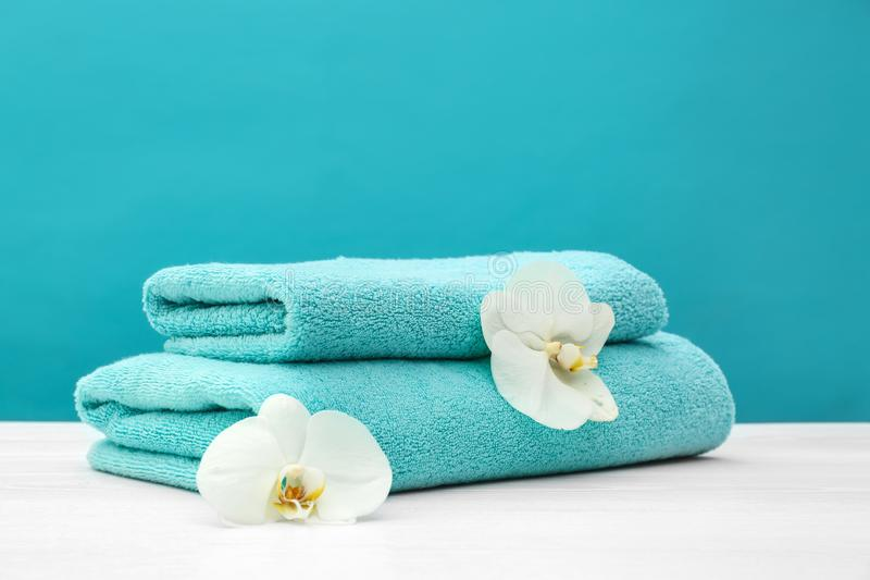 Stack of soft clean towels with beautiful flowers on table against color background. Space for text royalty free stock photos