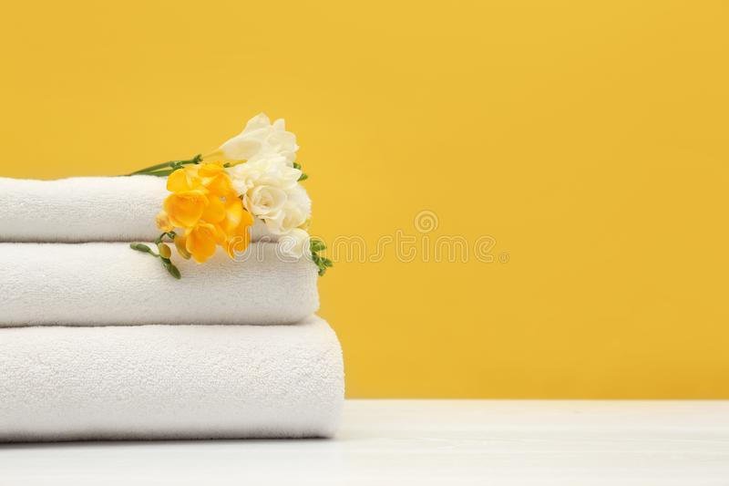 Stack of soft clean towels with beautiful flowers on table against color background. Space for text royalty free stock photography