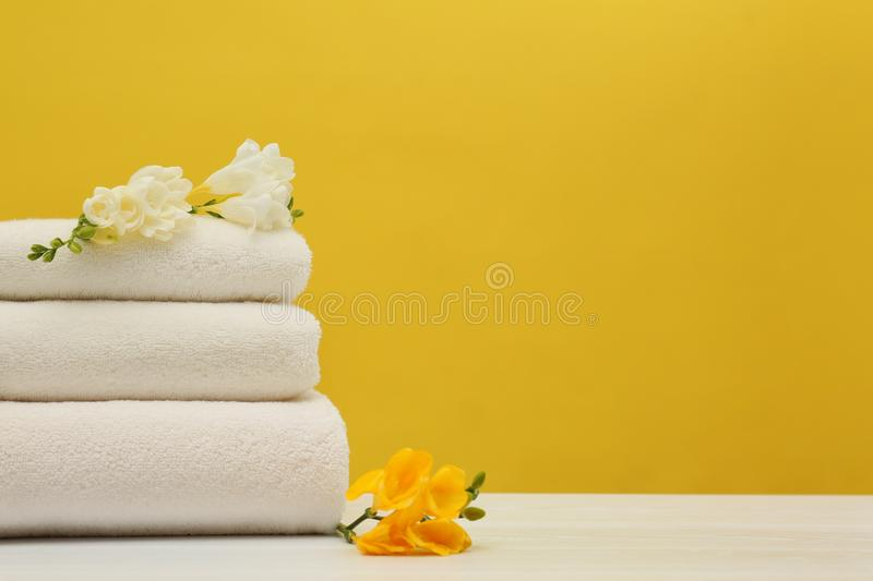 Stack of soft clean towels with beautiful flowers on table against color background. Space for text royalty free stock photo