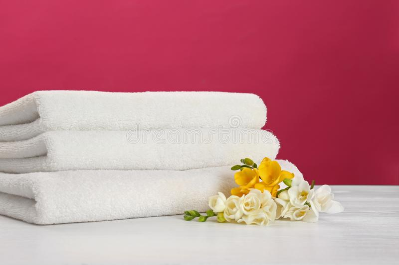 Stack of soft clean towels with beautiful flowers on table. Against color background. Space for text stock photo