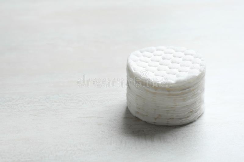 Stack of soft cotton pads on light background. Space for text stock photography