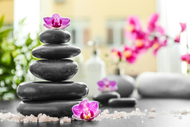 Stack of spa stones and scattered sea salt on dark table stock photography