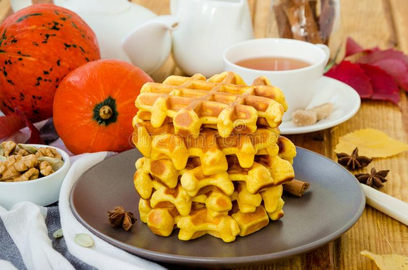 Stack of spicy pumpkin waffles on a dark plate with caramel sauce and whipped cream on a dark wooden background. stock photography