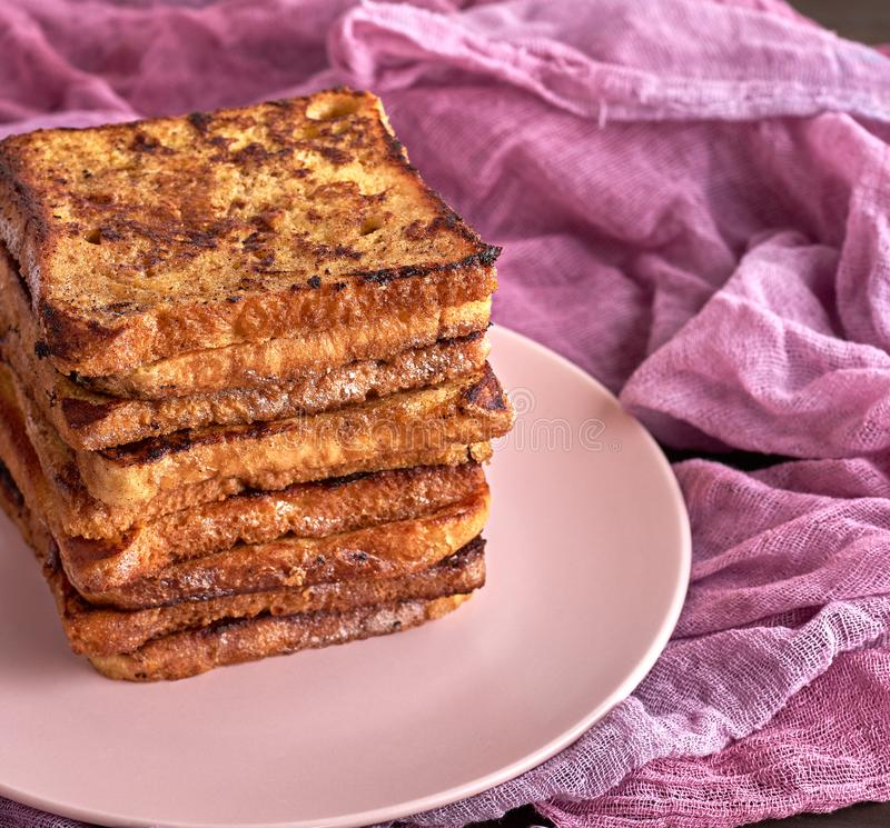 Stack of square pieces of fried bread slices on a pink ceramic round plate. Behind a cotton napkin. French toast stock photos