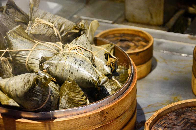 Stack of steamed chinese dumplings or zongzi in bamboo basket, sticky rice wrapped in bamboo leave for dumpling festival royalty free stock photo