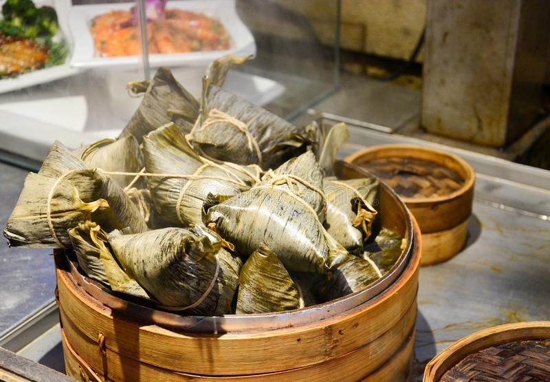 Stack of steamed chinese dumplings or zongzi in bamboo basket, sticky rice wrapped in bamboo leave for dumpling festival. Or dragon boat festival selective stock images