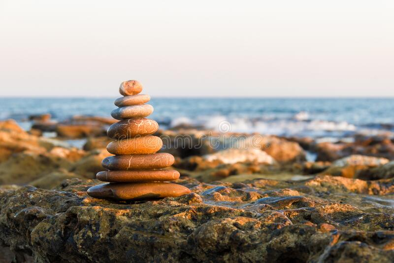 Stack of stones against blurred seascape, space for text. Zen concept. stock image