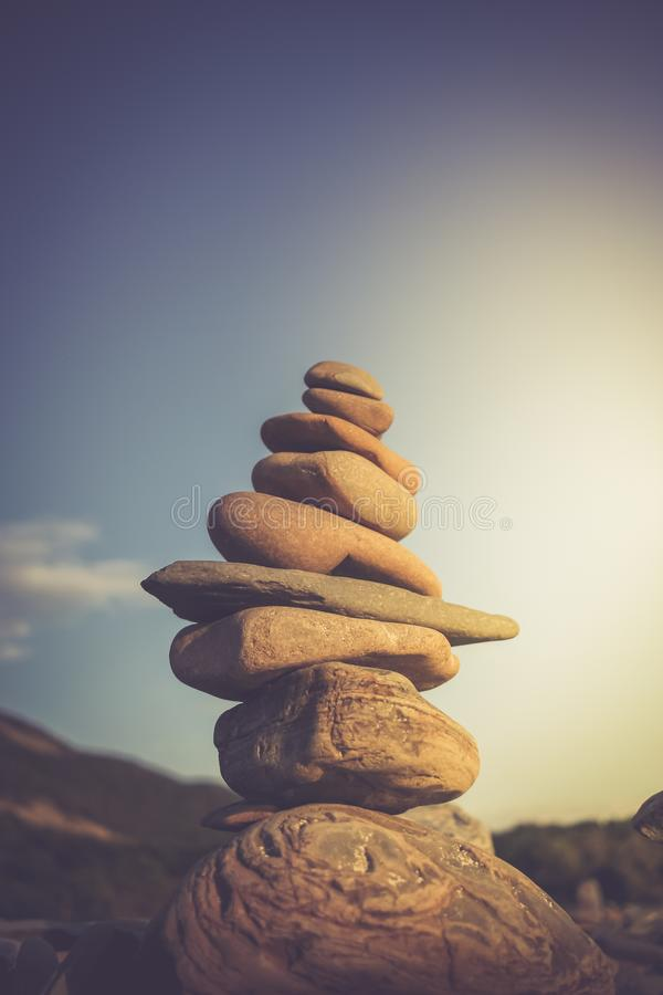 Stack of stones symbolizing Zen against sky. Toned image. Stack of stones symbolizing Zen against sky. Violet toned image royalty free stock photography
