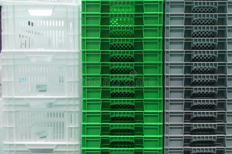 Stack Storage of new colourful white, grey and green plastic container crates royalty free stock images