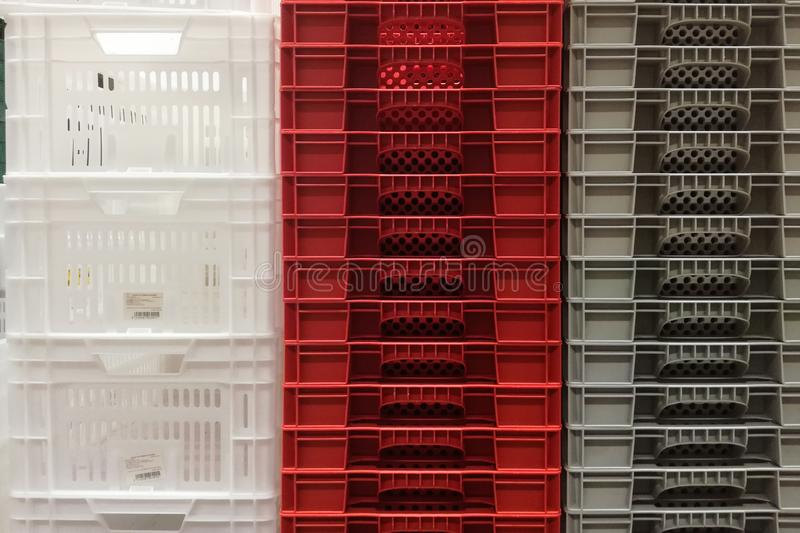 Stack Storage of new colourful white, grey and red plastic container crates royalty free stock photo